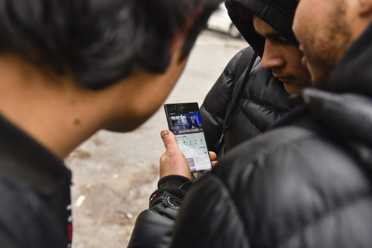 Migránsok a magyar közmédia határsértésről szóló tudósítását nézik okostelefonon a vajdasági Horgos központjában 2020. január 28-án.