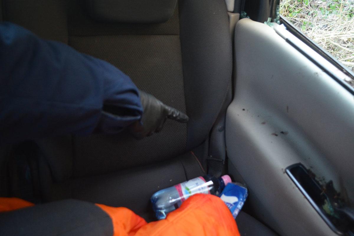 A rendőr mutatja, hogy nem használták a hátsó biztonsági övet az összetört autóban.