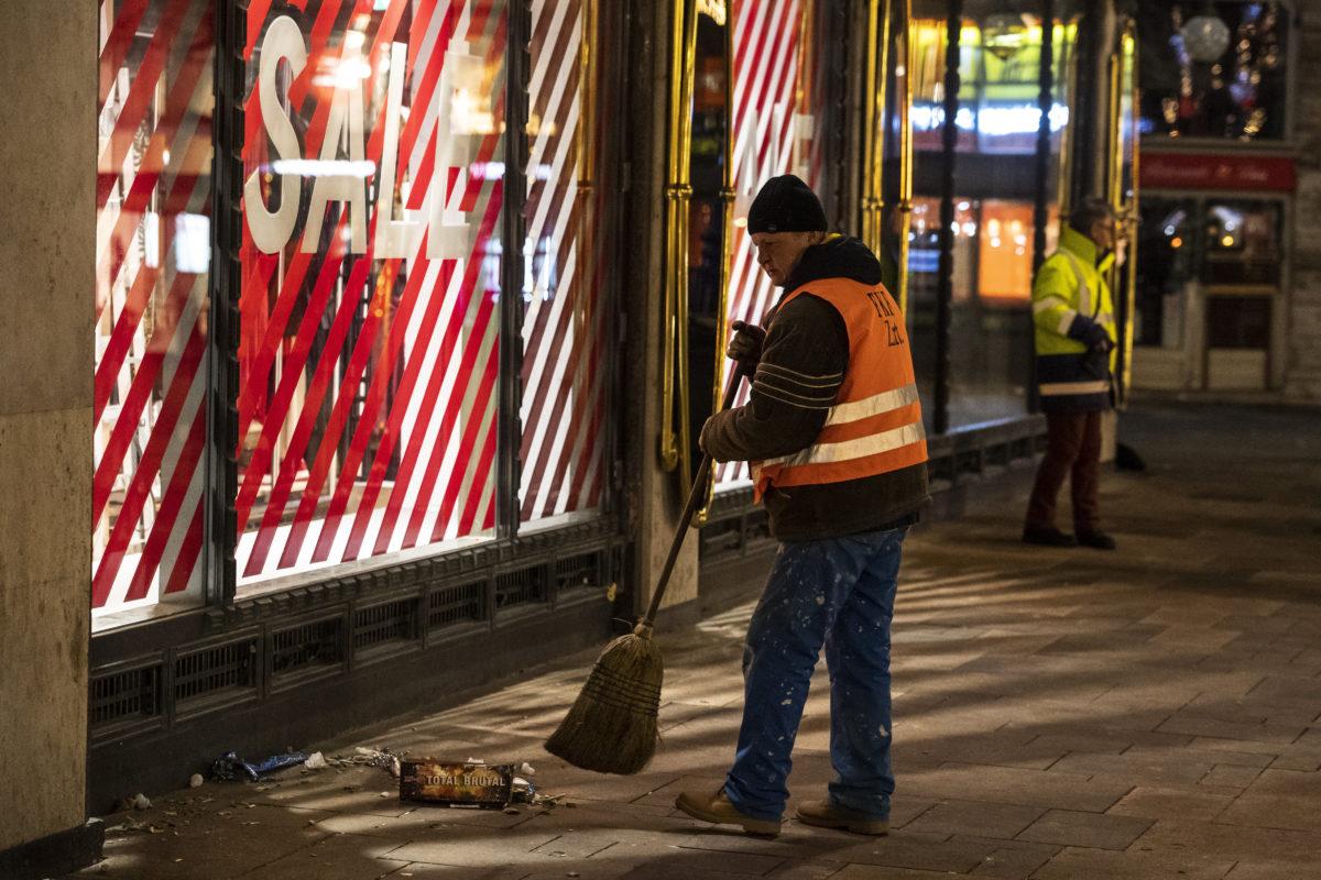 A szilveszteri ünneplés után maradt hulladékot takarítják a Fővárosi Közterület-fenntartó (FKF) Zrt. dolgozói a belvárosi Vörösmarty téren 2020. január 1-jén hajnalban.