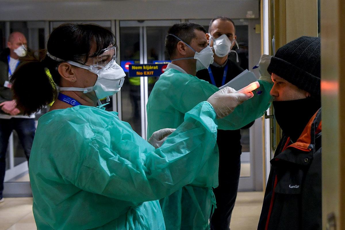 Olaszországból hazatért utasok testhőmérsékletét mérik a milánói járat érkezése után a debreceni repülőtéren 2020. február 25-én.