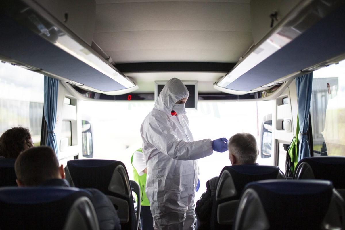 Török Róbert mentőápoló ellenőrzi egy érkező busz utasait a koronavírus-járvány miatt a letenyei határállomáson 2020. február 5-én.