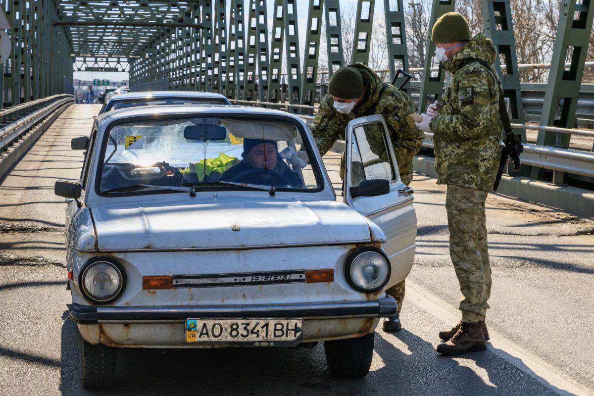 Védőmaszkot viselő ukrán határőrök mérik egy belépő gépkocsivezető testhőmérsékletét a Csaphoz közeli Tisza közúti határátkelőn, az ukrán-magyar határon 2020. február 25-én.