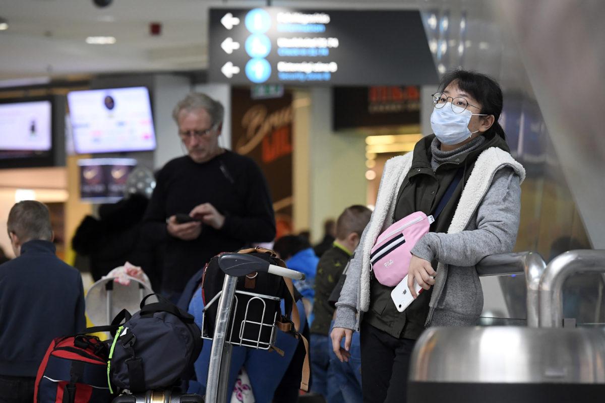 Egészségügyi maszkot visel egy utas a koronavírus-járvány miatt a budapesti Liszt Ferenc-repülőtéren 2020. február 4-én.
