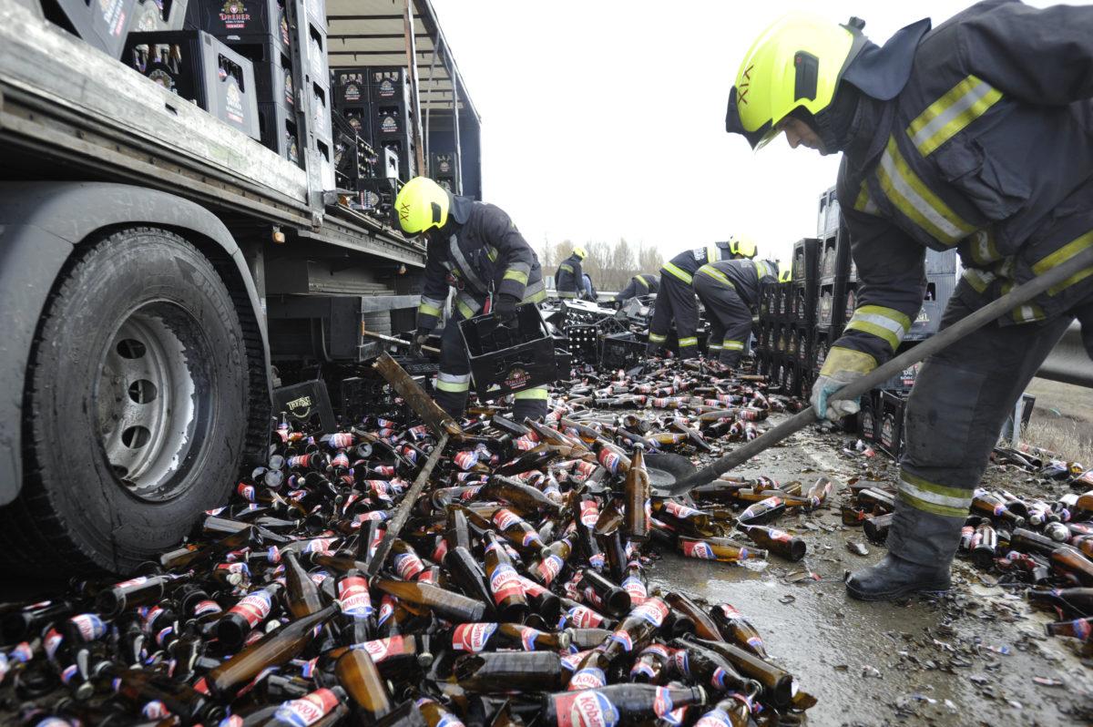 Tűzoltók takarítják fel és pakolják egy sörszállító kamion leborult rakományát az M0-ás autóútról az M4-es autópályára vezető felhajtónál Budapest határában 2020. február 27-én.