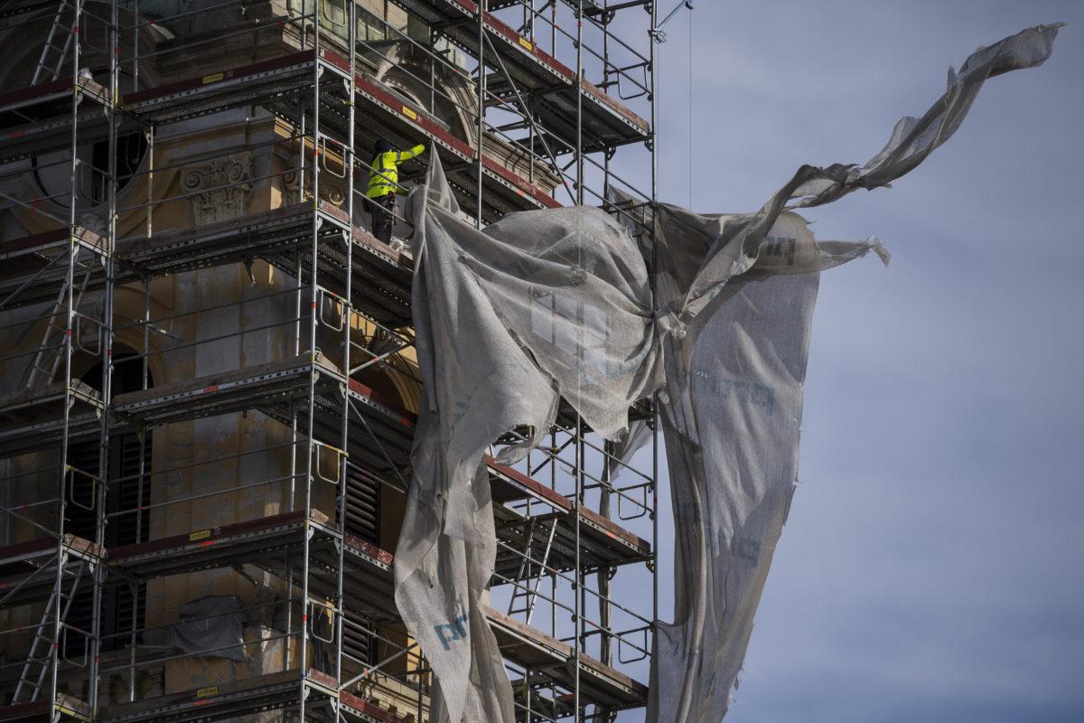 A viharos szélben leszakadt ponyvát igazítja egy munkás a Budapest-Józsefvárosi Szent József plébániatemplom állványzatán a VIII. kerületi Horváth Mihály téren 2020. február 5-én.