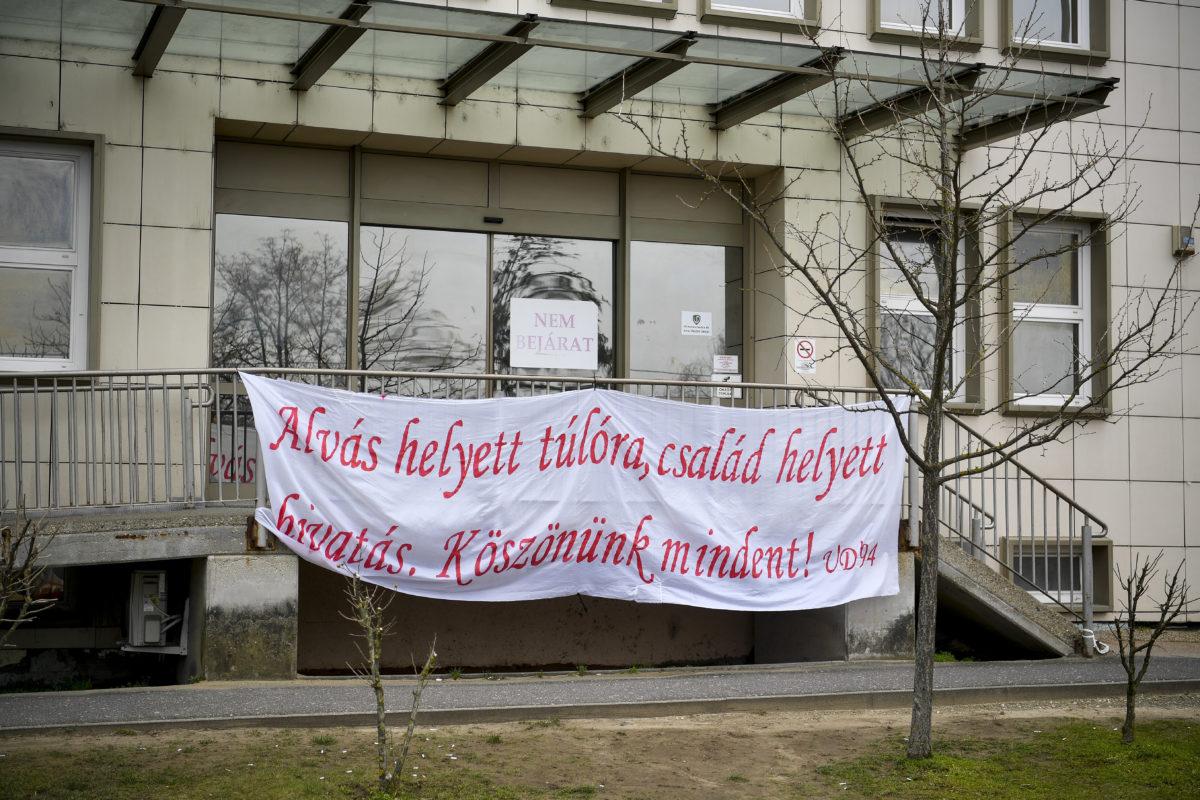 Alvás helyett túlóra, család helyett hivatás. Köszönünk mindent! feliratú molinó a Debreceni Egyetem Kenézy Gyula Egyetemi Kórház korlátján Debrecenben 2020. március 21-én.