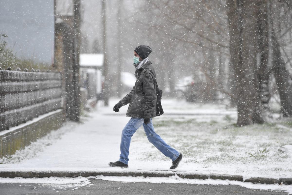 A koronavírus-járvány miatt szájmaszkot viselő férfi hóesésben Debrecenben 2020. március 23-án.