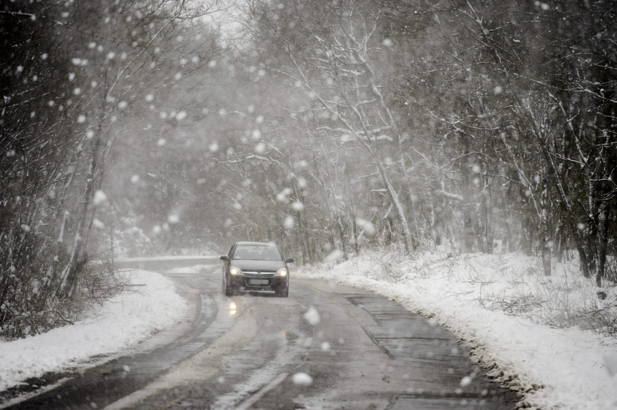 Egy autó halad a havazásban a Heves megyei Bátor közelében 2020. március 23-án.