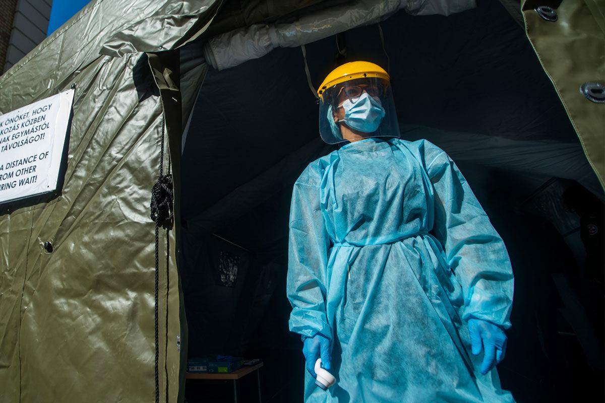 Védőfelszerelést viselő nővér áll a Honvédkórház Róbert Károly körúti székhelyén felállított elővizsgálati sátornál 2020. március 16-án.