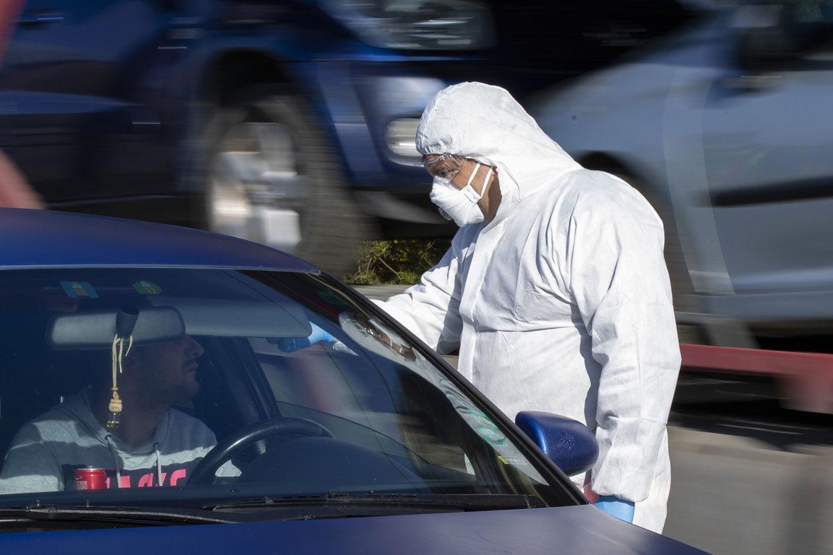 A tüdőgyulladást okozó új koronavírus-járvány miatt bevezetett határellenőrzésen mentő méri egy vezető hőmérsékletét a magyar-szlovén határ közelében, az M70-es autópálya csörnyeföldi pihenőhelyénél 2020. március 12-én.