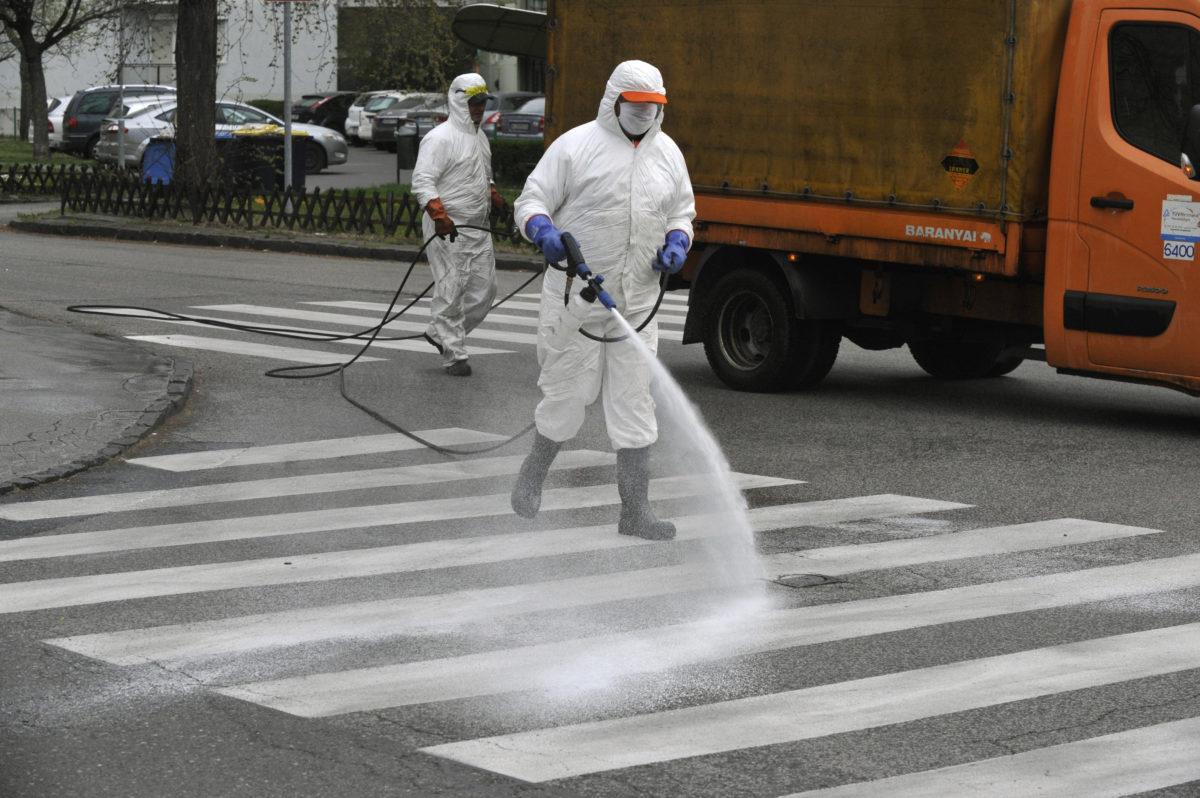 A zebrát fertőtlenítik a koronavírus-járvány miatt szakemberek az önkormányzat megbízásából védőfelszerelést viselő munkatársa a IX. kerületi Ifjúmunkás utcában, a József Attila-lakótelepen 2020. március 30-án.