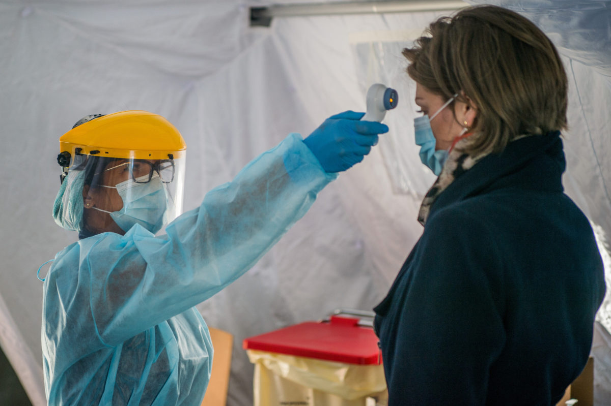 Védőfelszerelést viselő nővér megméri egy érkező testhőmérsékletét a Honvédkórház Róbert Károly körúti székhelyén felállított elővizsgálati sátorban 2020. március 16-án.