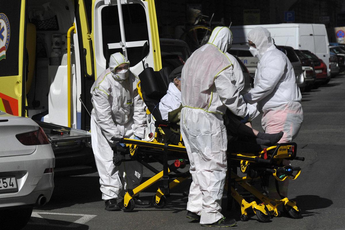 A Szent László kórházba visznek egy idős férfit a védőöltözetbe öltözött mentők a VI. kerületi Eötvös utcából 2020. március 24-én.