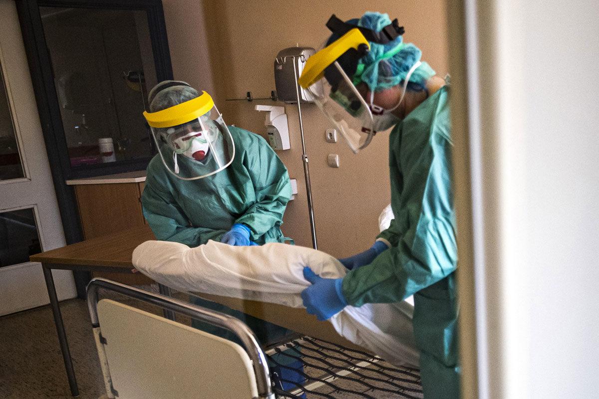 Védőfelszerelést viselő nővérek egy kórtermet készítenek elő a koronavírussal érintett új betegek fogadására kialakított egyik osztályon a fővárosi Szent László Kórházban 2020. március 16-án.