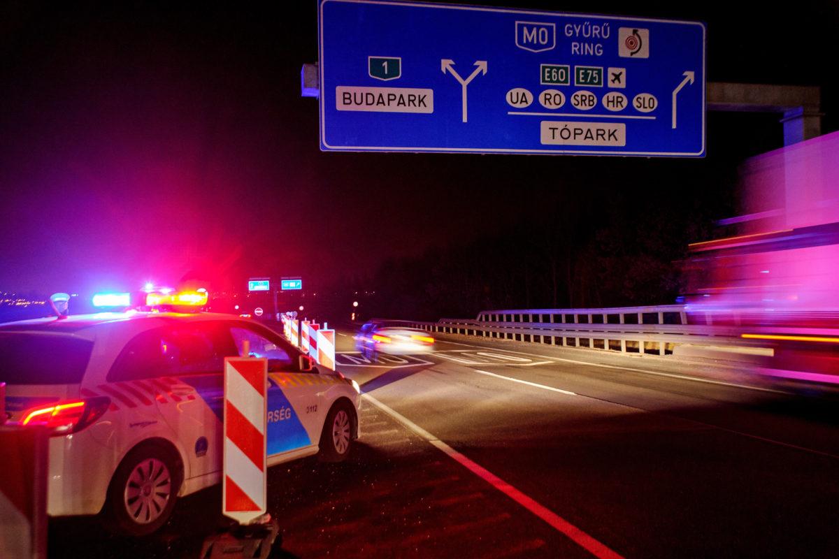 Rendőrök dolgoznak az M1 autópályán, az M0 autóút Románia és Szerbia felé vezető lehajtójánál, ahol a koronavírus-járvánnyal kapcsolatban meghozott kormányzati intézkedések alapján lezárták a Budapest felé vezető utat a Magyarországon átvonuló külföldi vendégmunkások előtt 2020. március 18-ra virradó éjjel.