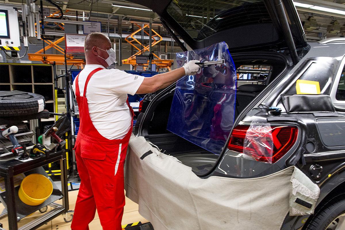 Dolgozó a koronavírus ellen védő műanyag lapot helyez egy autó csomagtere és utastere közé, mielőtt berakja a pótkereket az Audi Hungaria Motor Kft. győri gyárának járműszerelő részlegében 2020. április 27-én. Ezen a napon sikeresen újraindult az Audi Hungaria járműgyártása, mind a présüzemben, karosszériaüzemben, lakkozóban és a járműszereldében.