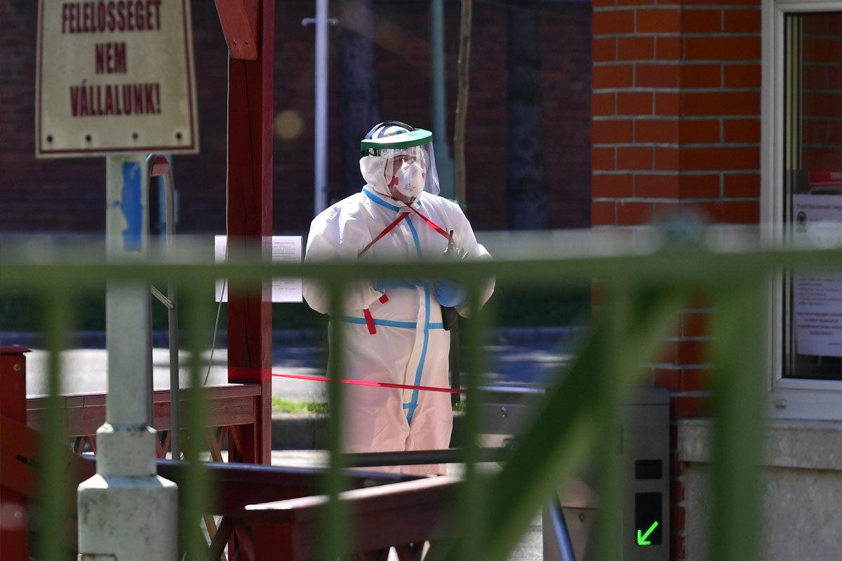 Védőruhát viselő férfi a fővárosi önkormányzat Pesti úti idősotthona udvarán 2020. április 9-én. Immár több mint százan megfertőződtek és öten meghaltak az intézményben, jelentette be Müller Cecília országos tisztifőorvos a koronavírus-járvány elleni védekezésért felelős operatív törzs online sajtótájékoztatóján.