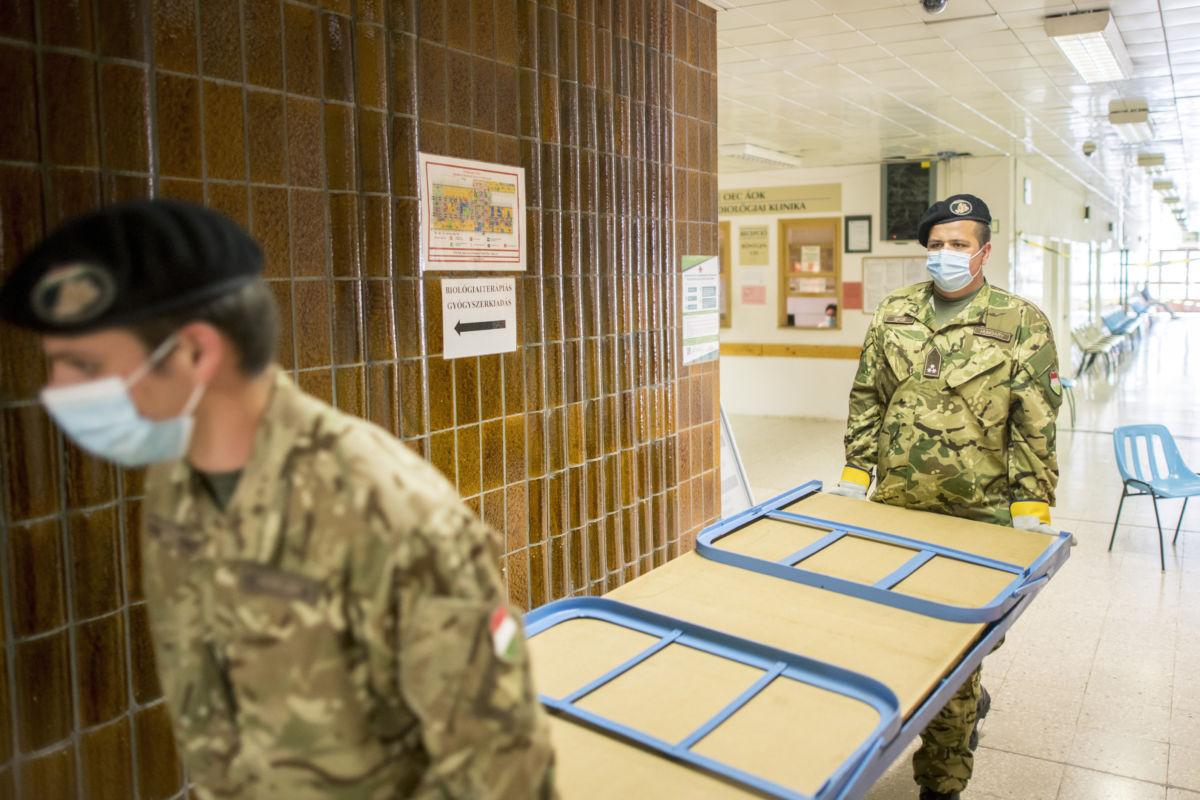 Katonák tábori ágyakat pakolnak a Pécsi Tudományegyetem Akác utcai klinikai tömbjében 2020. április 20-án.