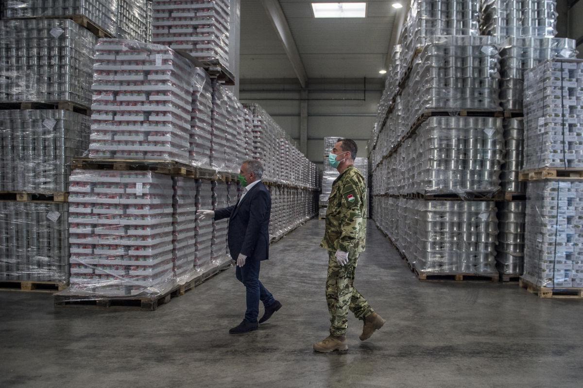 Kovács János (b), a Kecskeméti Konzervgyártó és Kereskedelmi Kft. ügyvezető igazgatója és Bús Gábor (j) mérnök ezredes, a Honvédelmi Irányító Törzs tagja megtekinti a cég raktárát 2020. április 17-én.