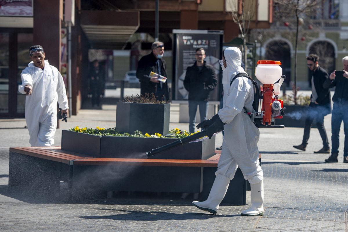 Vegyszeres fertőtlenítést végző szakemberek az egri Gárdonyi Géza téren a koronavírus-járvány idején, 2020. április 2-án.