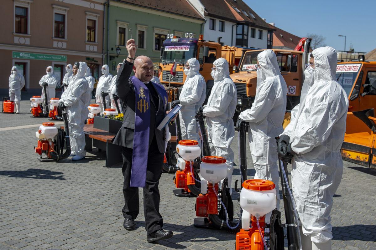 Czibere Zsolt plébániai kormányzó megáldja a vegyszeres fertőtlenítést végző szakembereket és eszközeiket az egri Gárdonyi Géza téren a koronavírus-járvány idején, 2020. április 2-án.