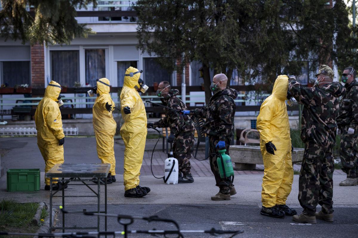 Védőruhába öltözött katonák ruházatát fertőtlenítik a fővárosi önkormányzat Pesti úti idősotthonában 2020. április 17-én.