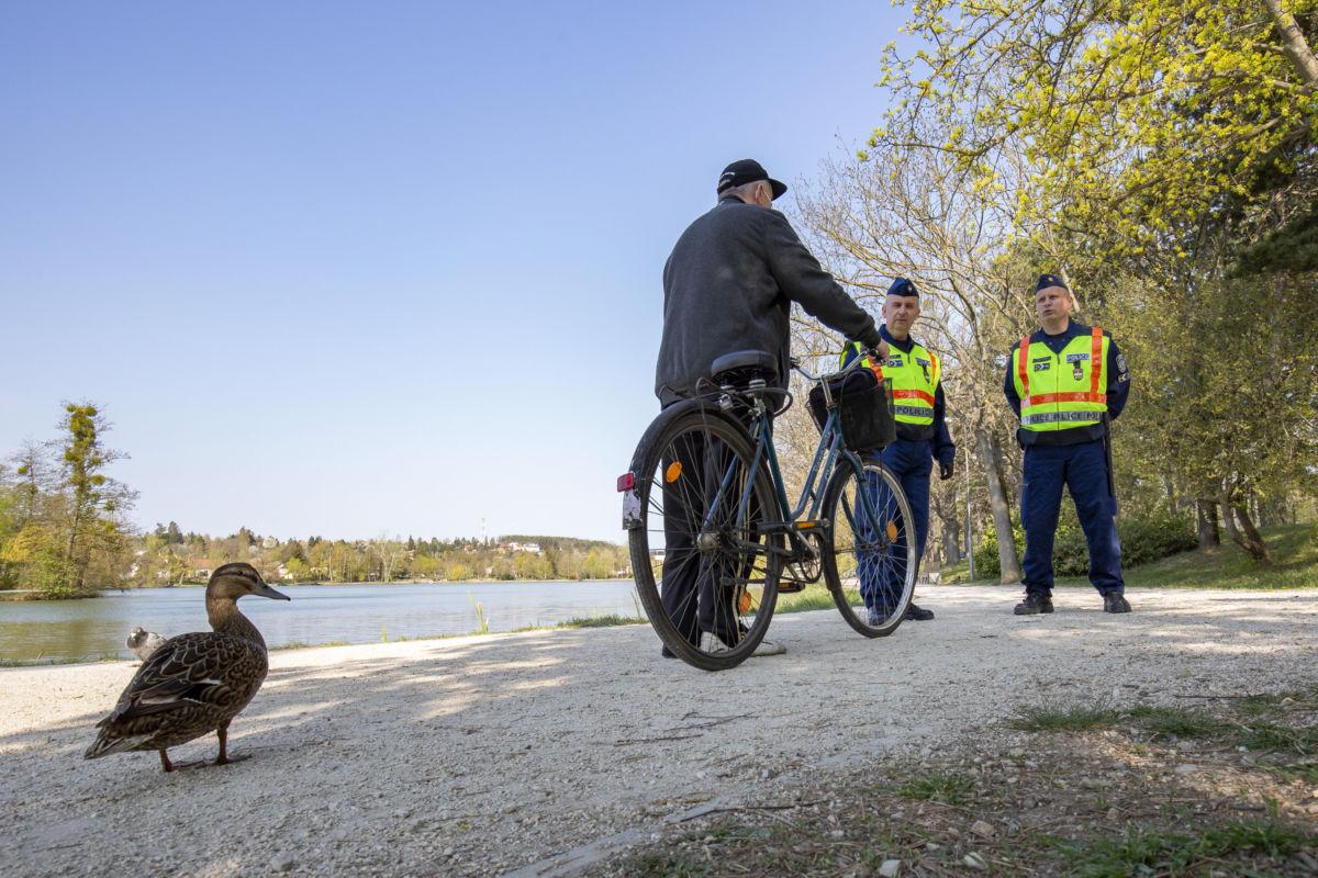 Járőröző rendőrök beszélgetnek egy férfival Szombathelyen, a Csónakázó-tó partján 2020. április 10-én.