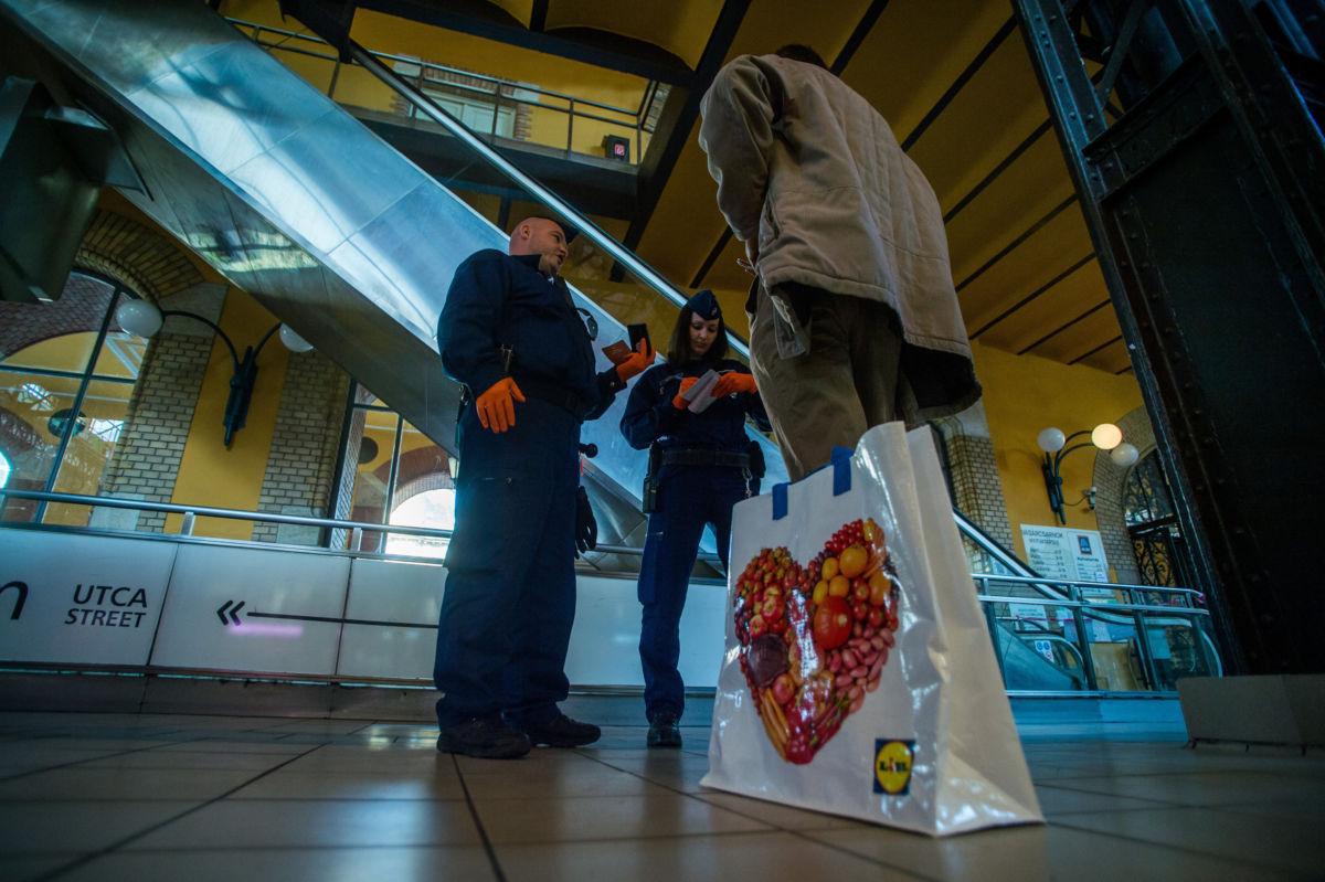 Rendőrök megbírságolnak egy 65 év alatti férfit a budapesti Fővám téri központi vásárcsarnokban 2020. április 9-én, mert 9 és 12 óra között csak a 65 felettiek vásárolhatnak.