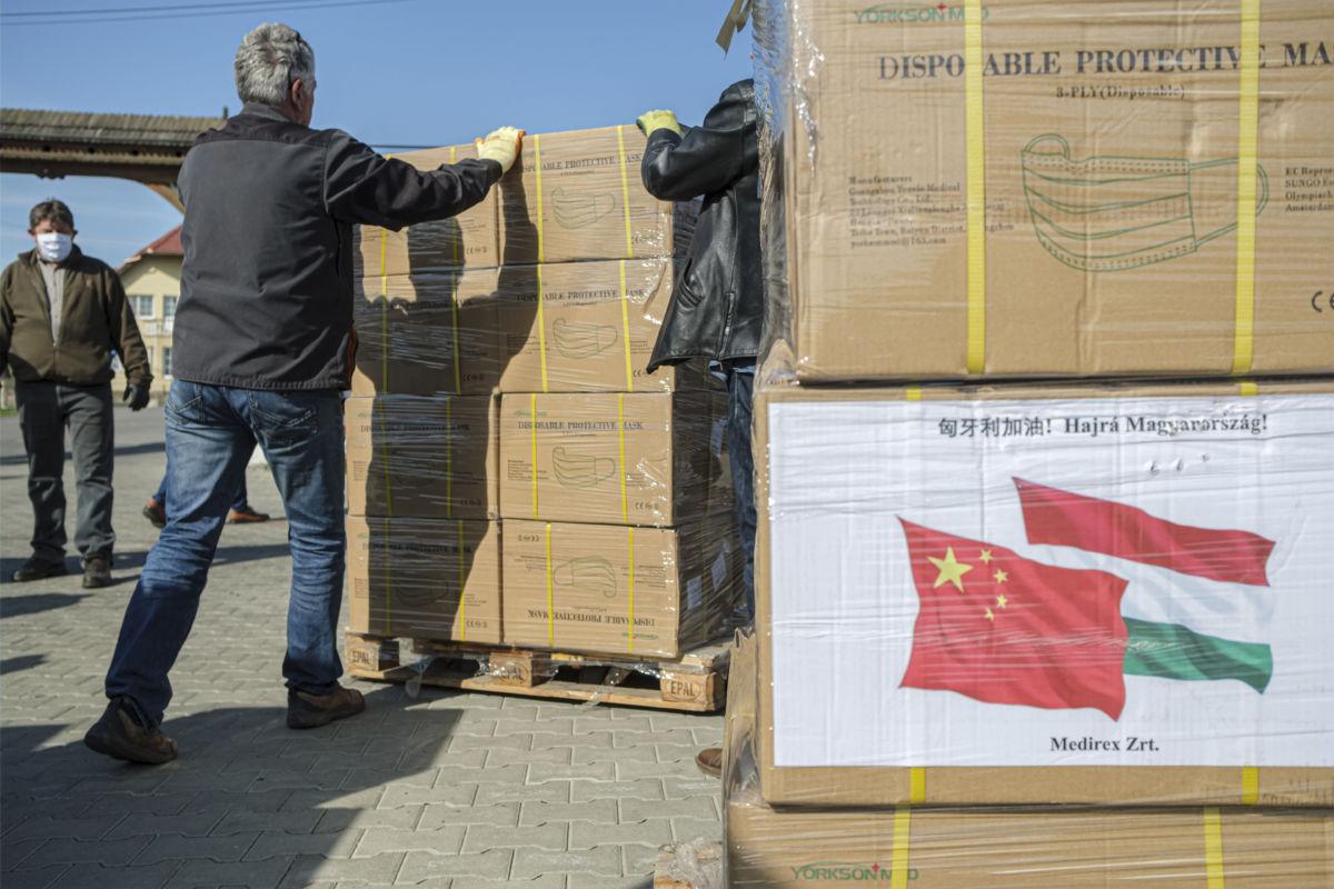 A magyar kormány egészségügyi védőfelszereléseket és fertőtlenítőszereket tartalmazó adományát pakolják Farkaslakán, a polgármesteri hivatal udvarán 2020. április 11-én.