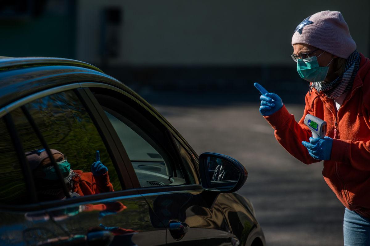 A koronavírus-járvány miatt az érkezők testhőmérsékletét mérik és az előírások betartására figyelmeztetik a beengedés előtt az Országos Korányi Pulmonológiai Intézet bejáratánál Budapesten 2020. április 17-én.