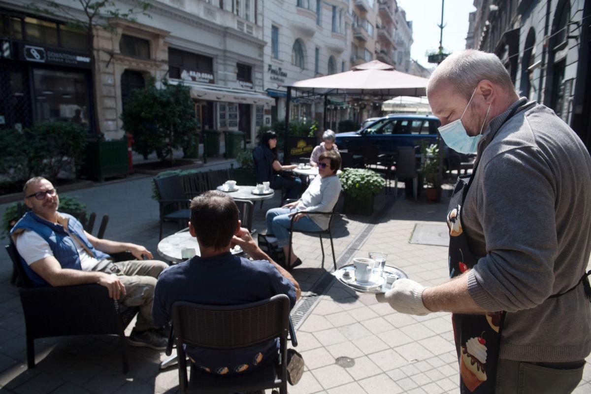 Egy vendéglős felszolgál egy kávézó teraszán a Ráday utcában 2020. május 18-án.