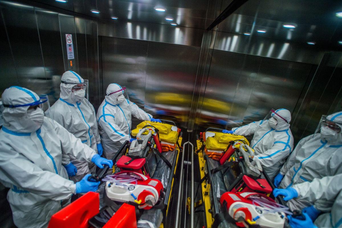 Védőfelszerelésbe öltözött mentők érkeznek az Országos Korányi Pulmonológiai Intézetbe, hogy elszállítsanak egy koronavírussal fertőzött beteget 2020. május 5-én.