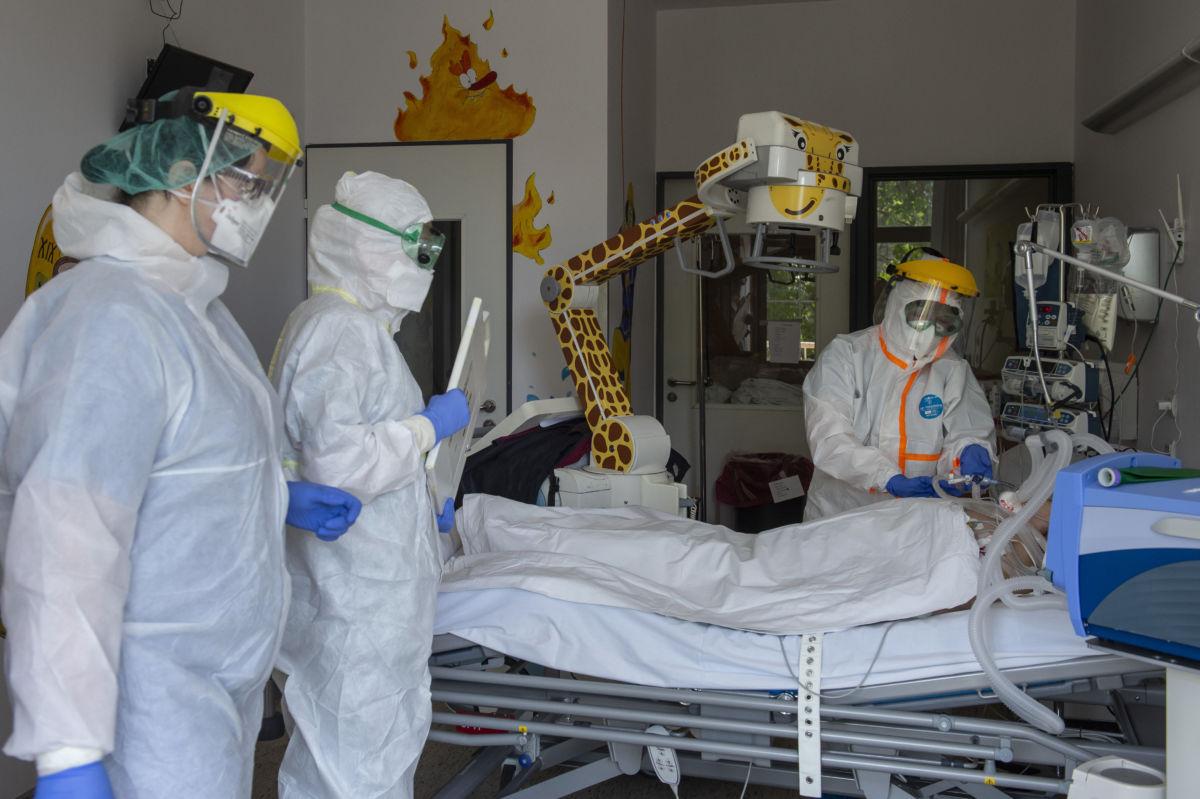 Védőfelszerelést viselő orvos és ápolók ellátnak egy beteget a koronavírussal fertőzött betegek fogadására kialakított osztályon a fővárosi Szent László Kórházban 2020. május 8-án.