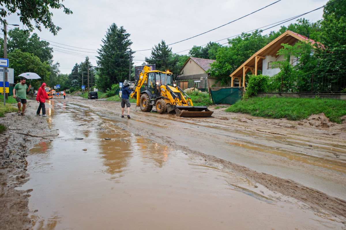 Munkagép a 10-es főút sárral és aszfaltdarabokkal borított szakaszán a vihar után Pilisborosjenőn 2020. június 14-én. A Pest megyei községben a lezúduló esővíz egy mezőgazdasági területről a földet, valamint az útburkolatot elsodorva elöntötte és járhatatlanná tette a 10-es főút egy szakaszát.