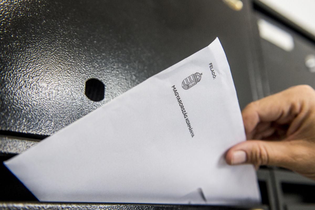Kézbesítő nemzeti konzultációs kérdőívet tartalmazó levelet dob postaládába egy kecskeméti társasházban 2020. június 15-én.