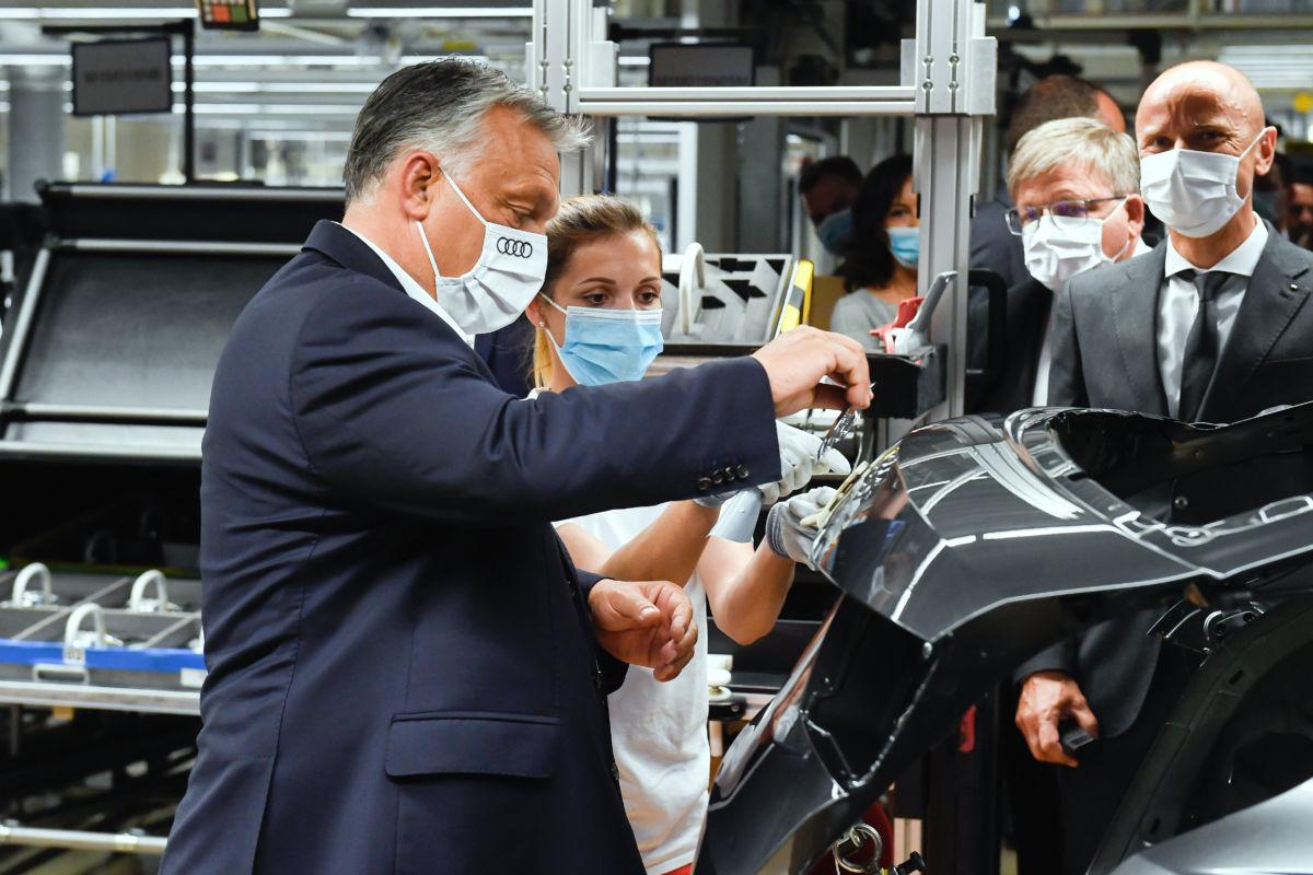 Orbán Viktor miniszterelnök emblémát ragaszt fel egy készülő autóra a győri Audi-gyárban 2020. június 15-én.