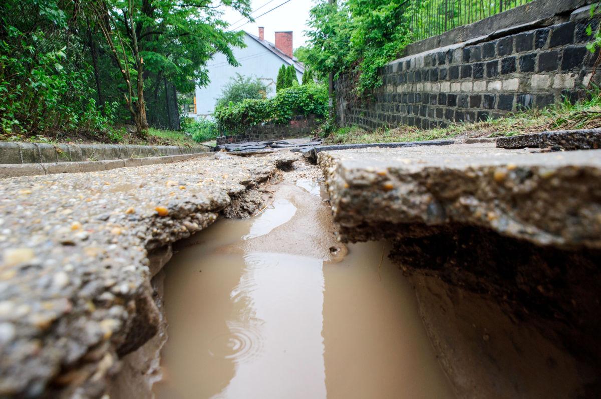 A vihar után járhatatlanná vált úttest Pilisborosjenőn 2020. június 14-én. A Pest megyei községben a lezúduló esővíz egy mezőgazdasági területről a földet, valamint az útburkolatot elsodorva elöntötte és járhatatlanná tette a 10-es főút egy szakaszát.