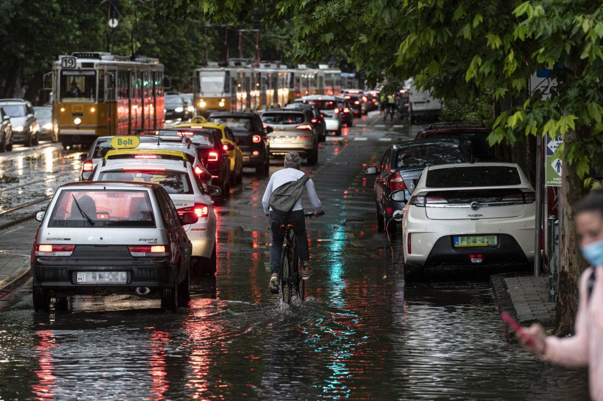 Kerékpáros, valamint autók és villamosok az esővízzel elöntött Bartók Béla úton a főváros XI. kerületében a vihar után 2020. június 17-én.