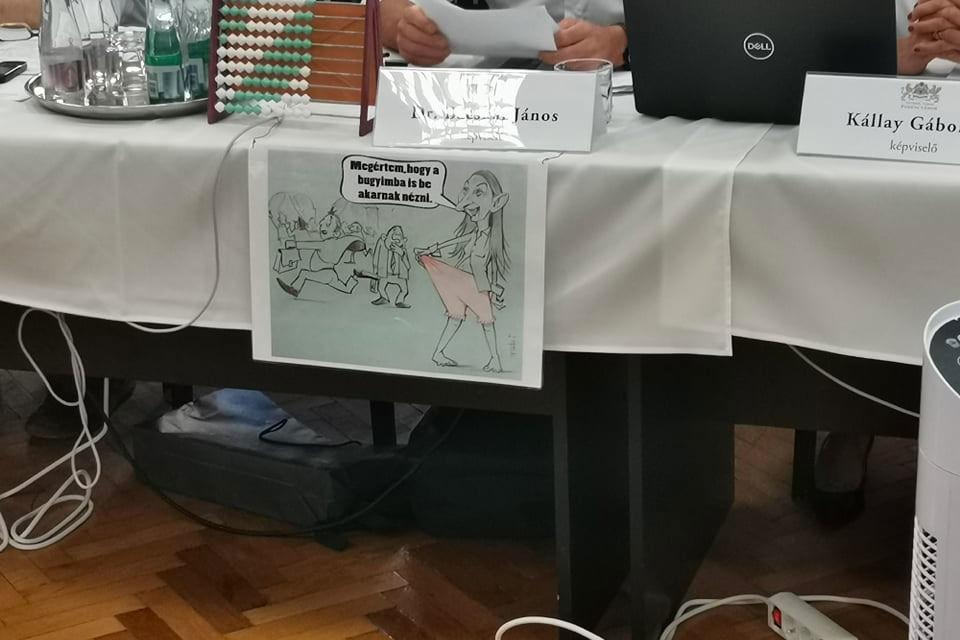 A fideszes Bácskai János hirdeti a keresztény, konzervatív humort az asztalára akasztott karikatúrával.