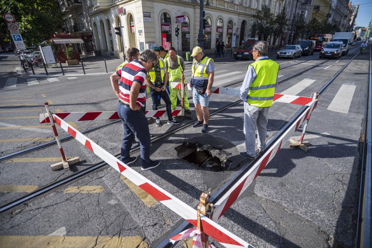 Szakemberek vizsgálják a villamos sínek között beszakadt útpályát a Vámház körúton 2020. július 15-én.