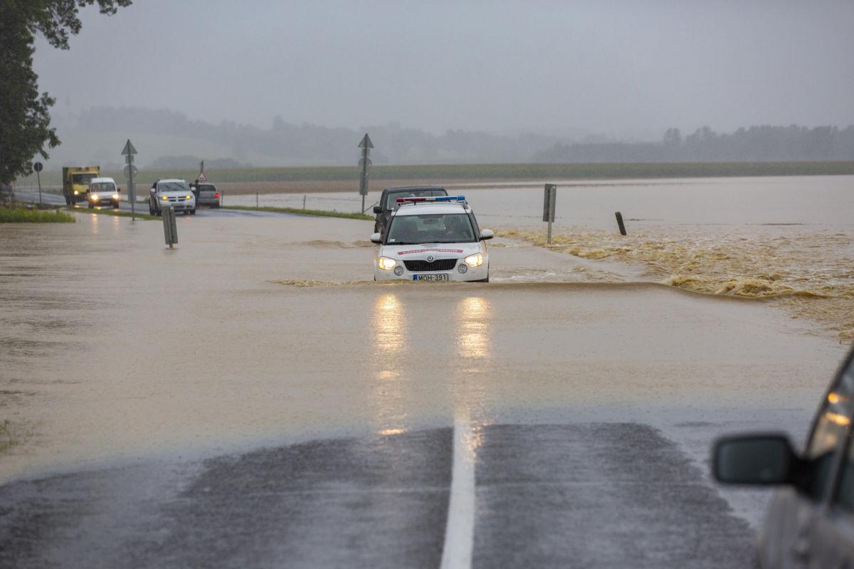A katasztrófavédelm gépjárműve és egy terepjáró halad a nagy esőzés miatt vízzel elárasztott Csurgót és Gyékényest összekötő úton, a Somogy megyei Porrogszentkirály közelében 2020. július 25-én.