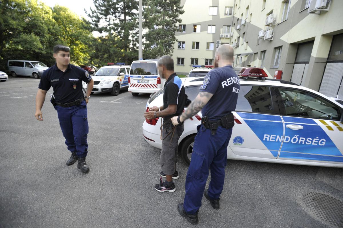 Rendőrök vezetik elő 2020. augusztus 28-án a budaörsi rendőrkapitányság udvarán azt az 55 éves férfit, aki a nyomozás adatai szerint egy budaörsi házban egy bárddal megsebesítette, és kirabolta két ismerősét.