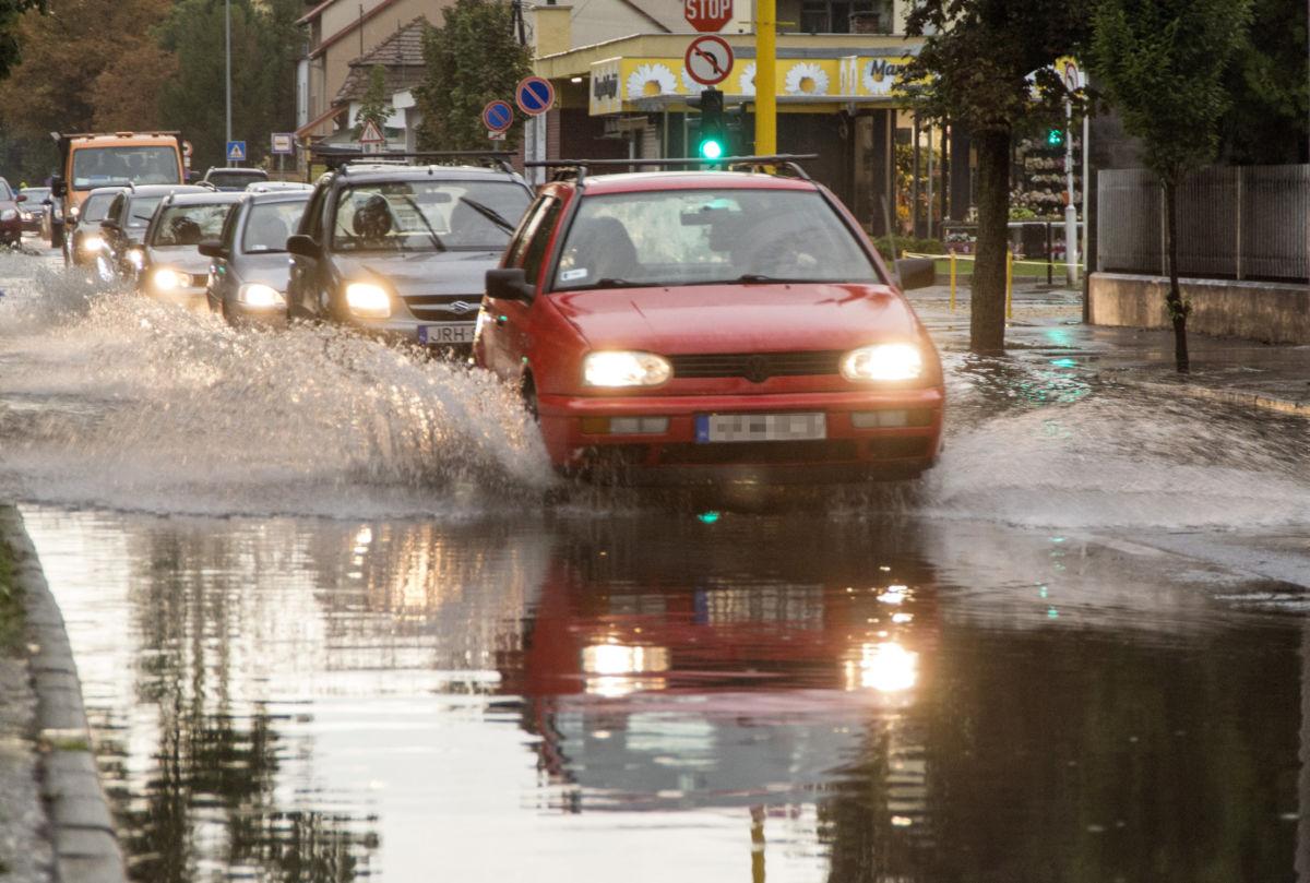Személyautók haladnak a heves zápor után esővízzel borított győri Mónus Illés utcában 2020. augusztus 17-én.