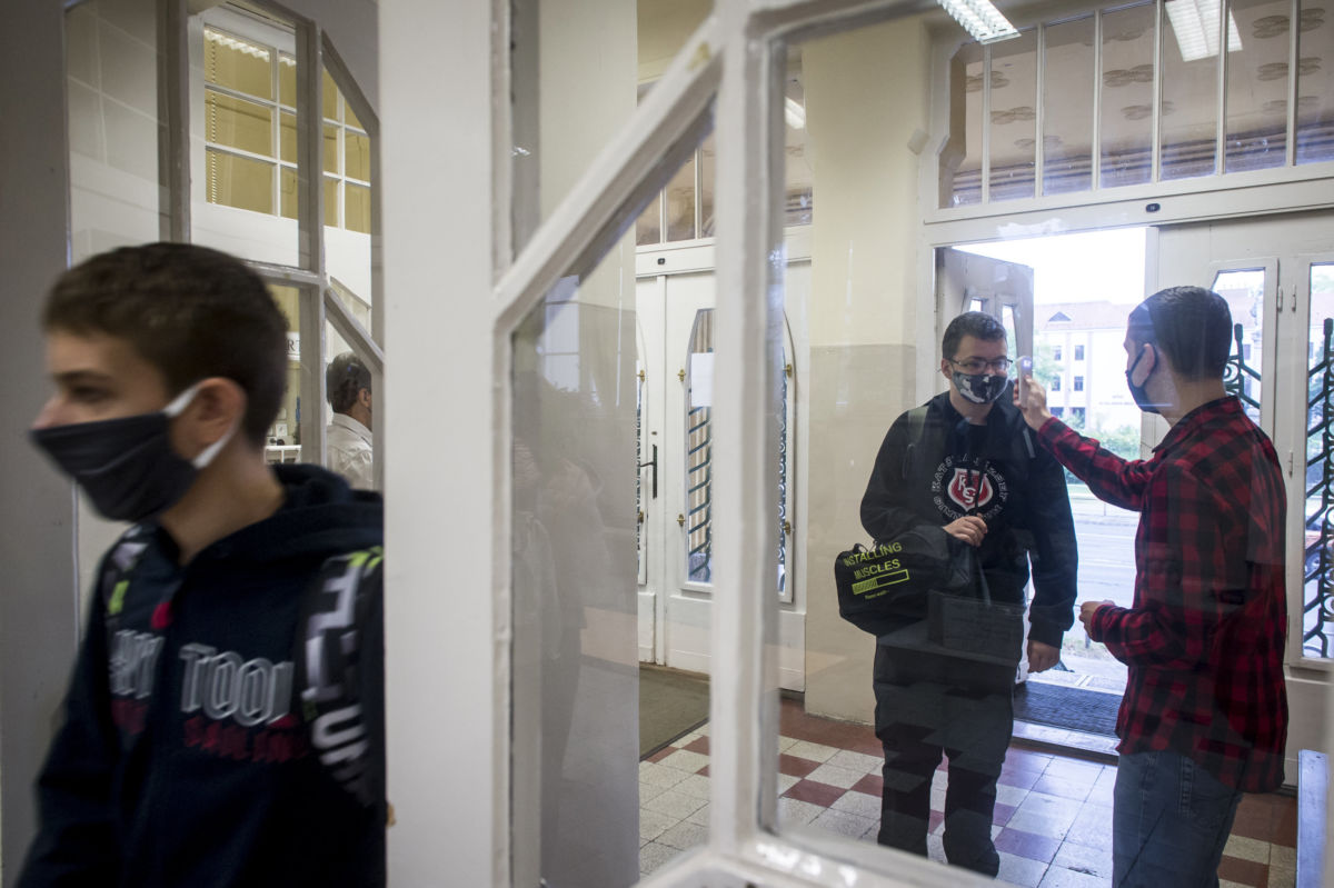 Kézi digitális hőmérővel ellenőrzik az iskolába érkező diákok testhőmérsékletét a Kecskeméti Katona József Gimnázium bejáratában 2020. szeptember 30-án.