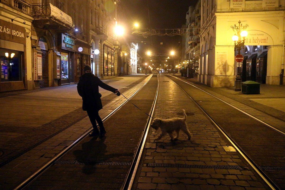 Kutyát sétáltat egy nő a miskolci Széchenyi utcában a kijárási tilalom idején 2020. november 14-én este.