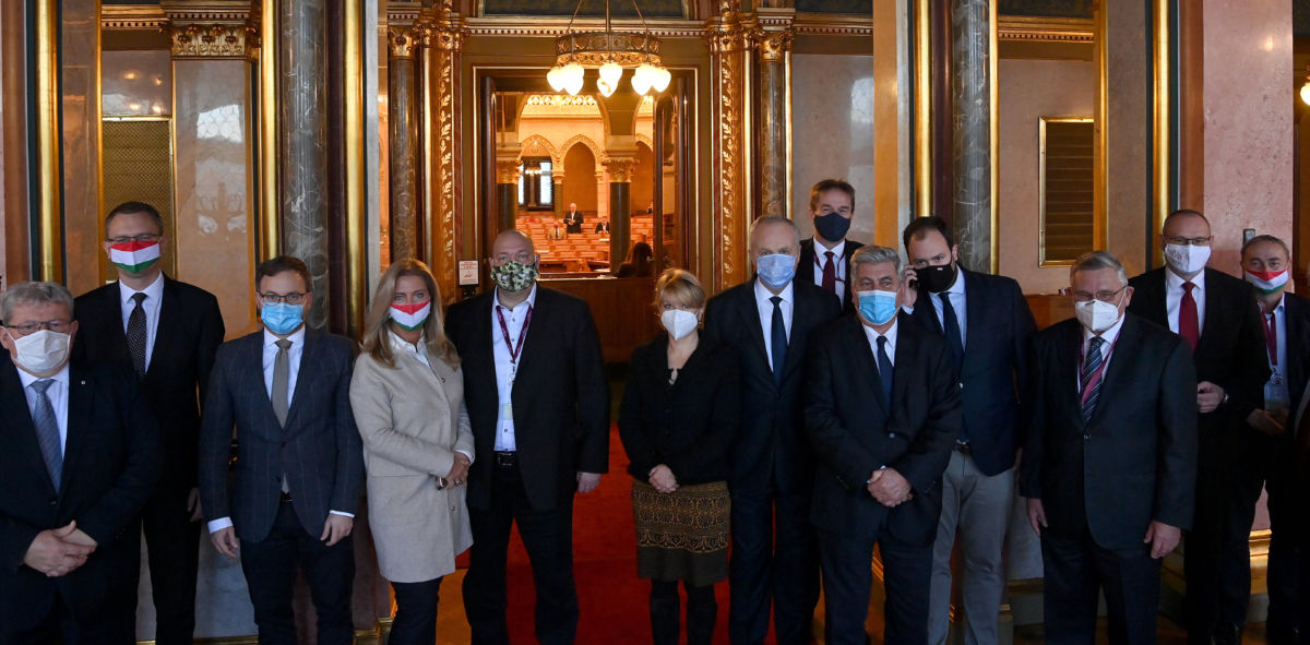 Kormánypárti (Fidesz-KDNP) képviselők az Országház folyósóján, miután kivonultak az ülésteremből Korózs Lajos, az MSZP képviselője (háttérben) napirend előtti felszólalásakor az Országgyűlés plenáris ülésén 2020. november 17-én.