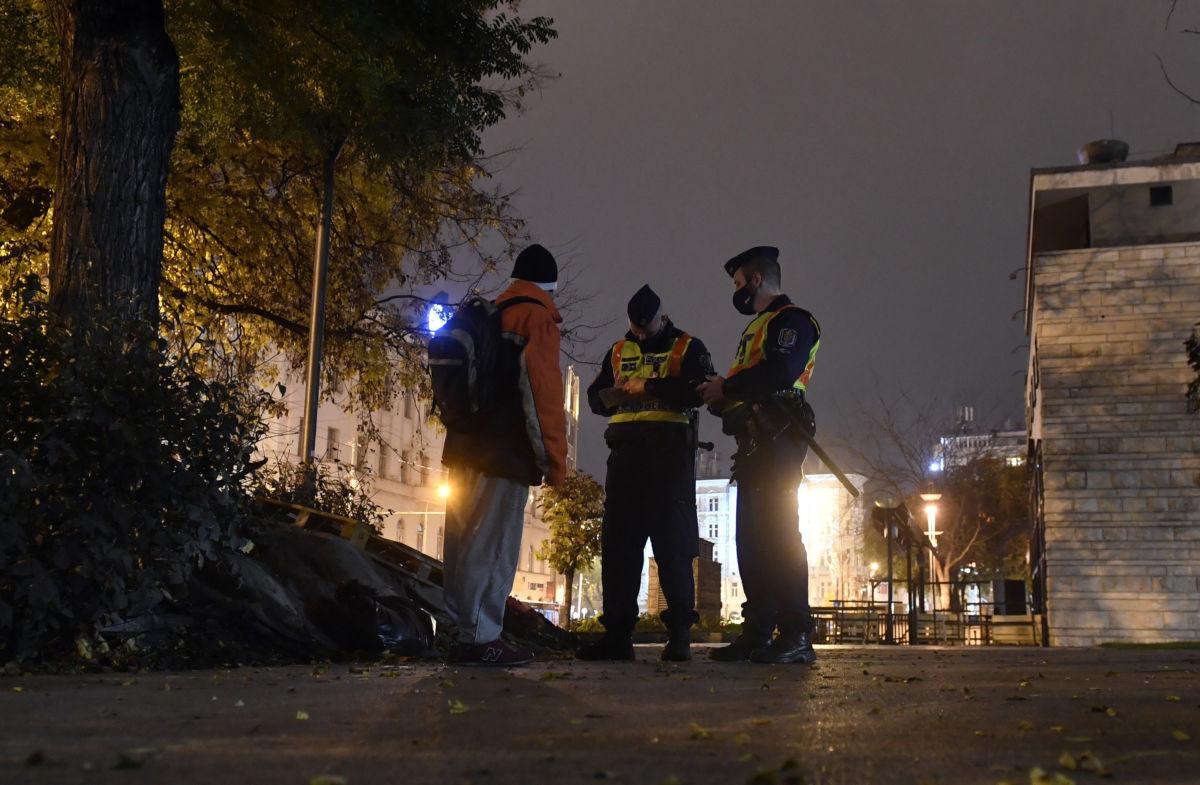Rendőrök igazoltatnak a koronavírus-járvány második hulláma miatt elrendelt kijárási tilalom idején a belvárosi Erzsébet téren 2020. november 11-én.