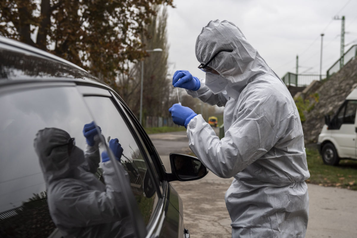 Koronavírusteszthez vesz mintát az Országos Mentőszolgálat (OMSZ) munkatársa az OMSZ Pók utcai szűrőbuszánál Óbudán 2020. november 13-án.