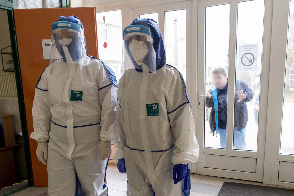 A koronavírus-teszteket végző, védőruhát viselő egyetemi hallgatók érkeznek a Mosonmagyaróvári Fekete István Általános Iskolába 2020. november 24-én.