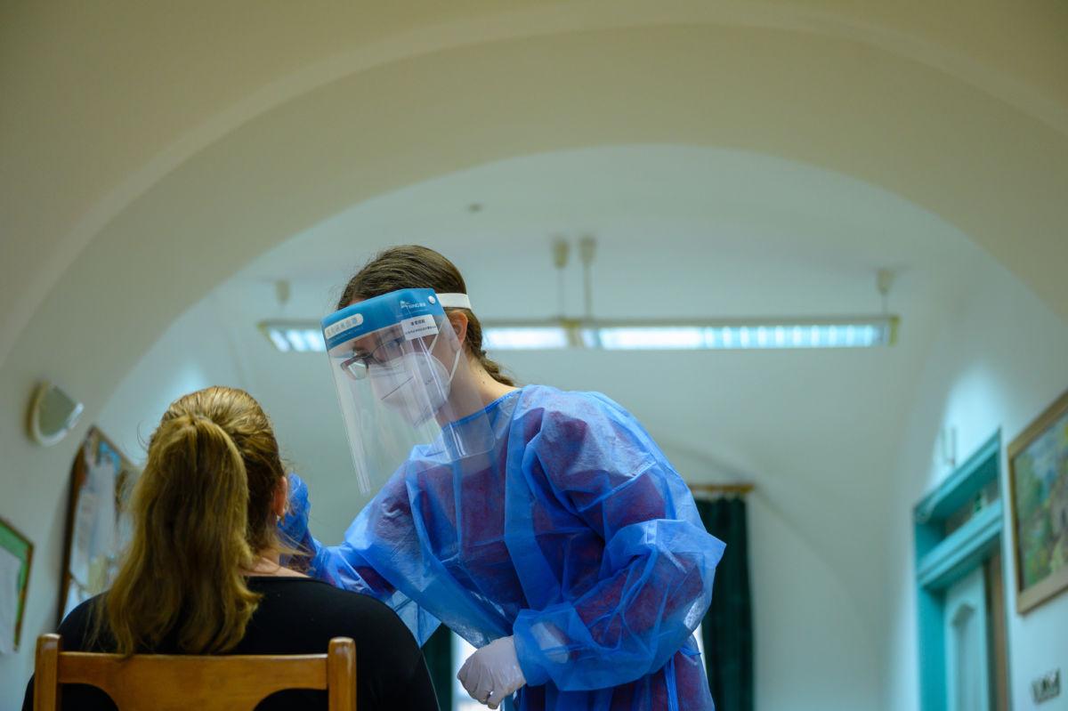 Koronavírus-teszthez vesz mintát a Semmelweis Egyetem gyógyszerész hallgatója a Mesevár Német Nemzetiségi Óvoda egyik munkatársától a Veszprém megyei Pápakovácsiban 2020. november 24-én.